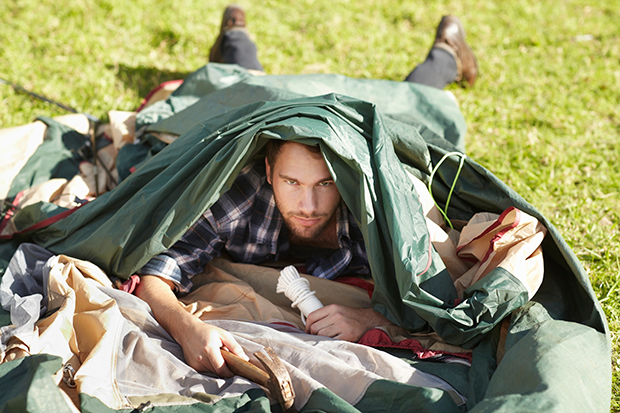 man exhausted from setting up tent